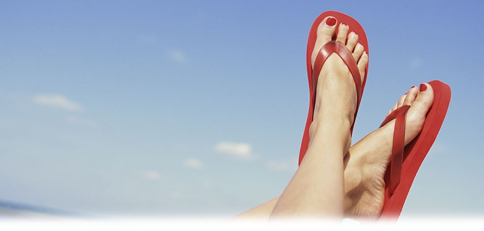 Feet in red flip flops with blue sky in background